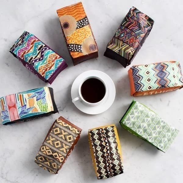A cup of coffee surrounded by pouches of different types of coffee