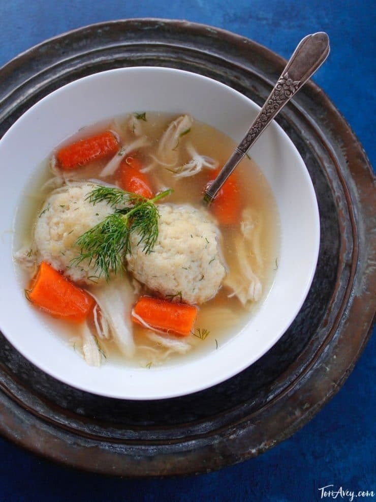 A bowl of chicken soup with carrots and matzo balls.