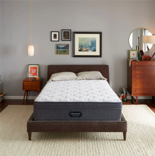 A brand-new mattress on a bed frame in a clean bedroom