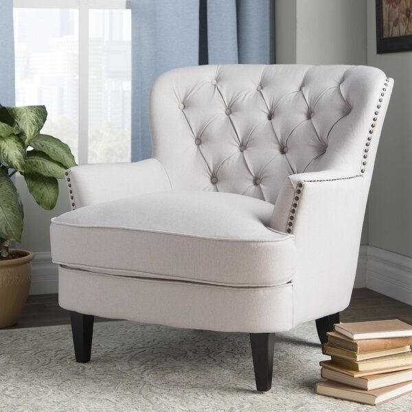 "The chair, with small wooden legs, tufting on the back, and nailhead trim around the edges of the arm and head rest, in ""natural,"" which is an off-white color"