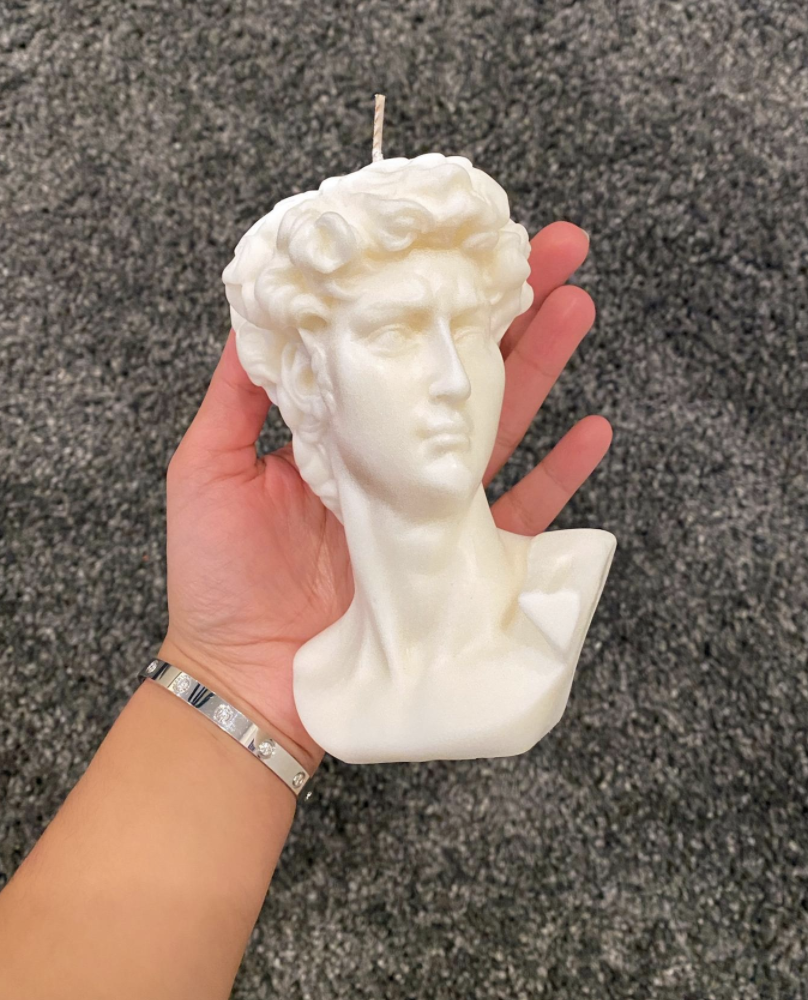 Person holding David bust candles