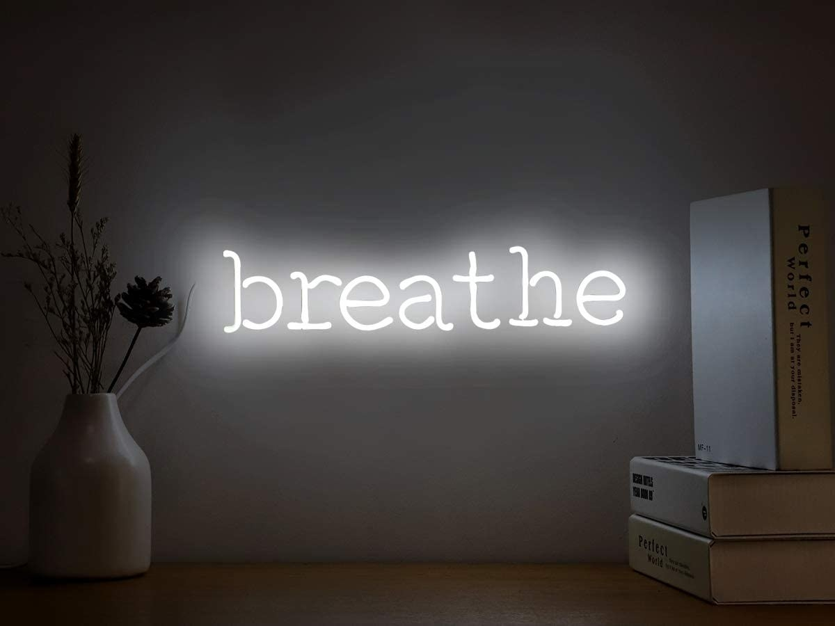 """A white neon sign that says """"breathe"""" mounted on a wall"""
