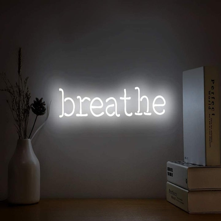 """A white neon sign that says """"breathe"""""""