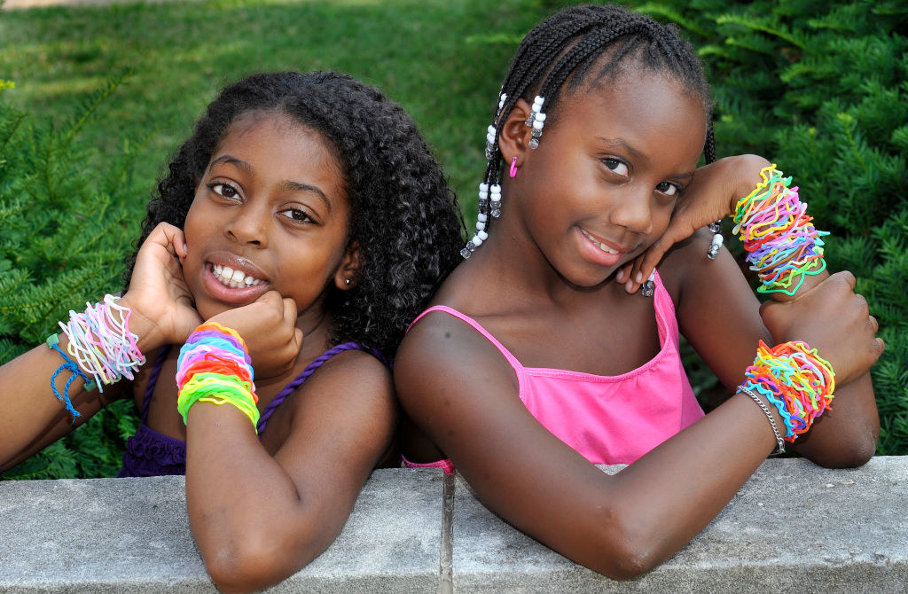 Two young girls wearing tons of silly bandz on their wrists
