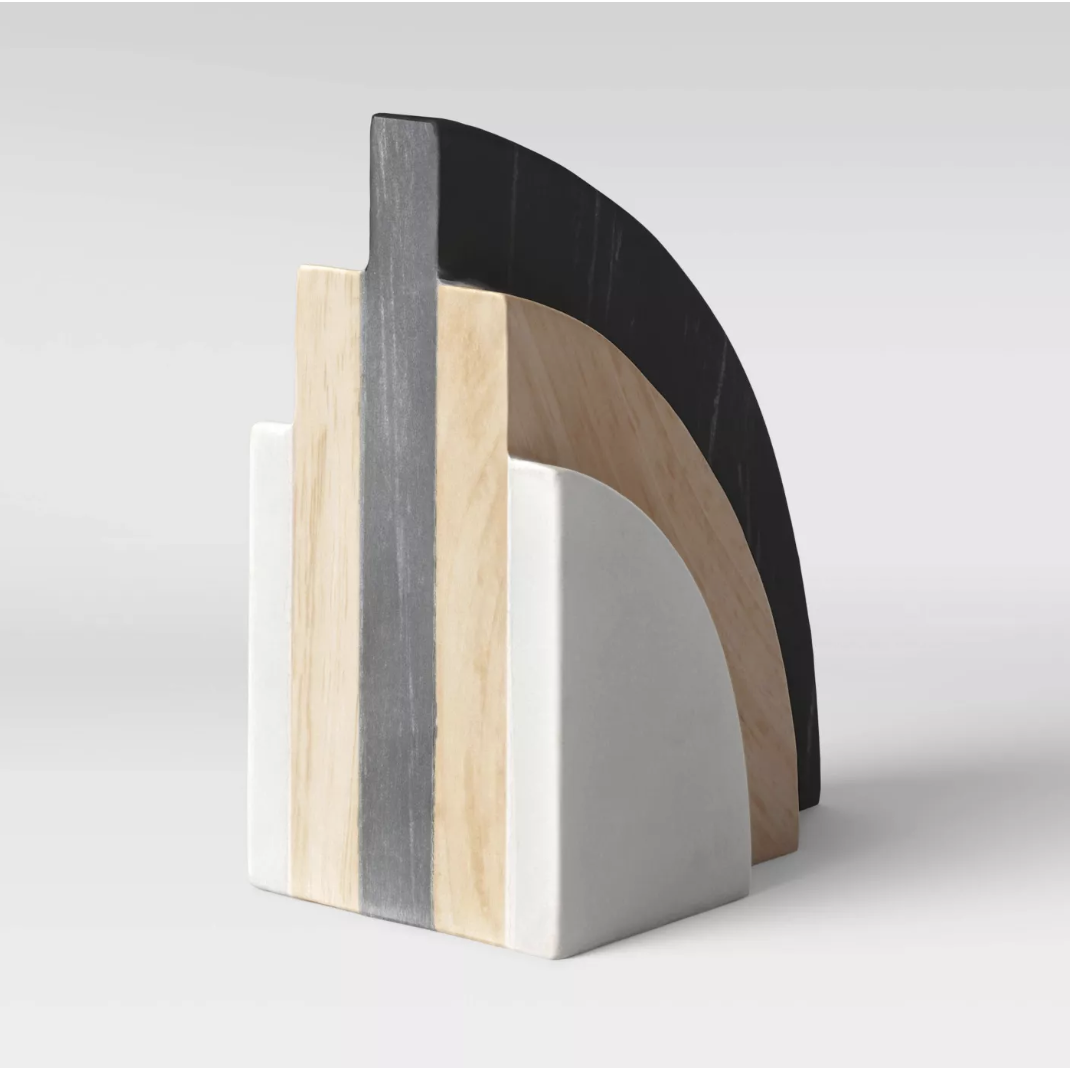 A curved bookend with layers of white, light wood, and black