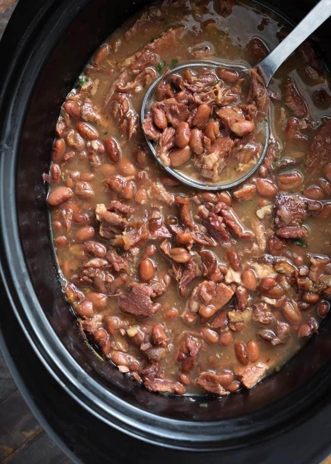 A slow cooker full of ham hocks and beans.
