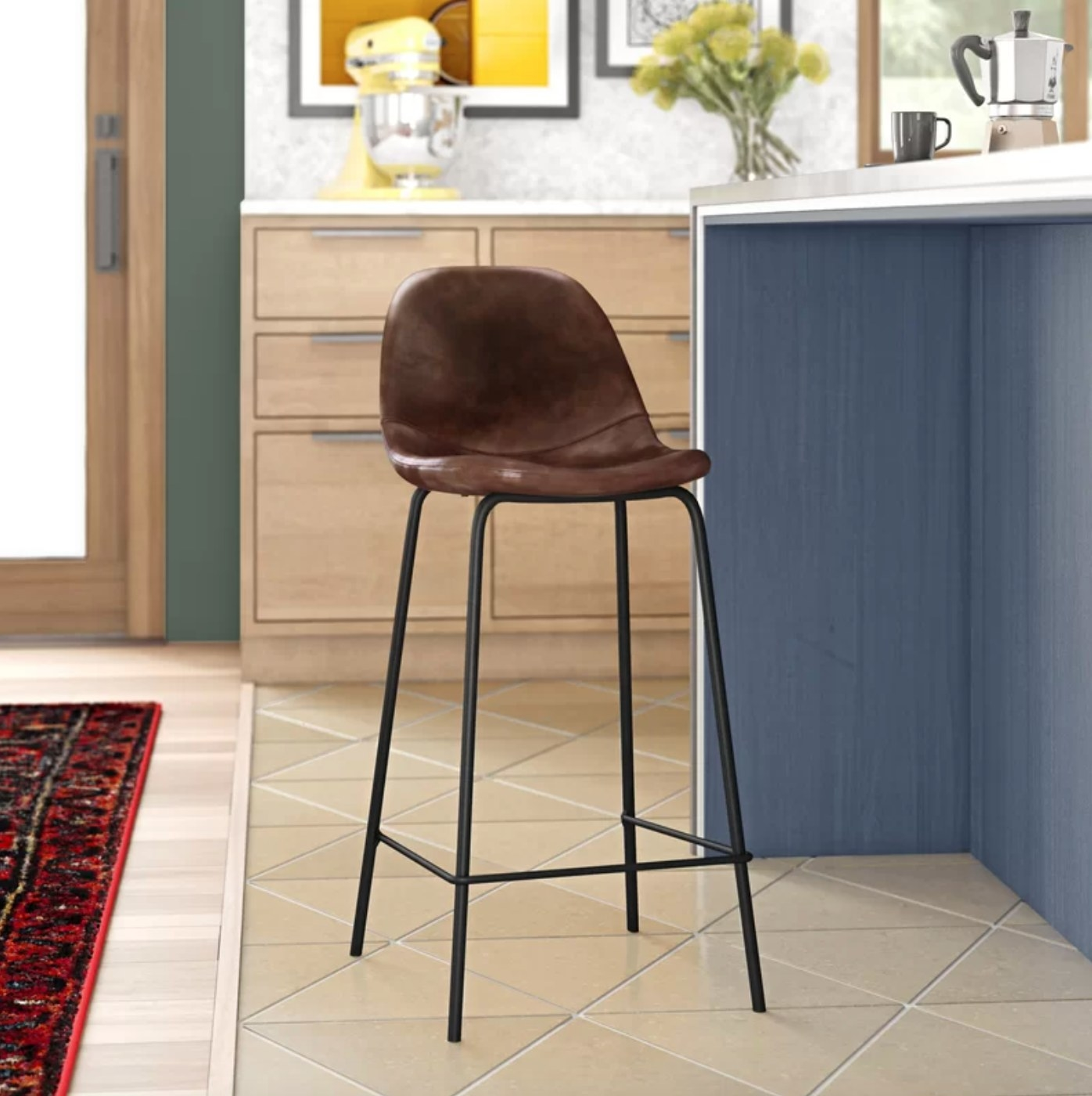 One of the kitchen stools with black legs and a brown leather seat