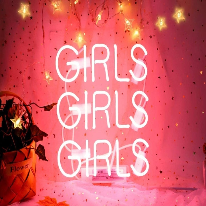 """A pink neon sign that says """"girls girls girls"""""""