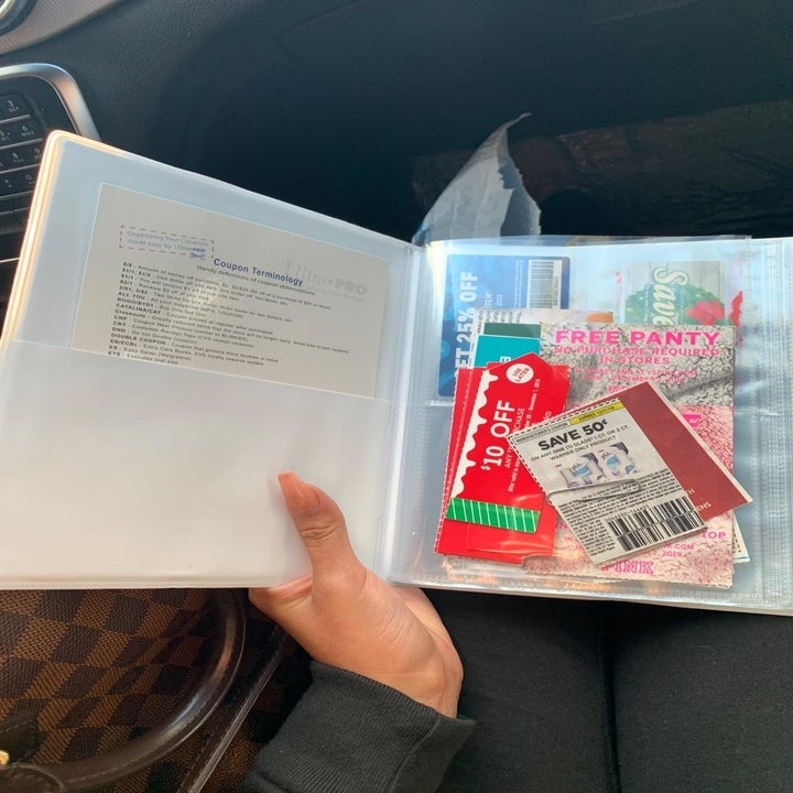 Reviewer with folio open to show interior pocket as well as pages of clear slots for coupons
