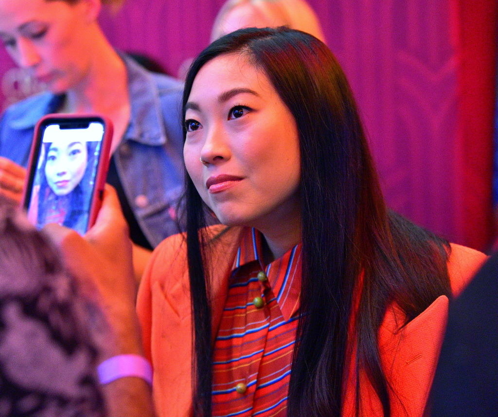 A fan taking a photo of Awkwafina on their cellphone