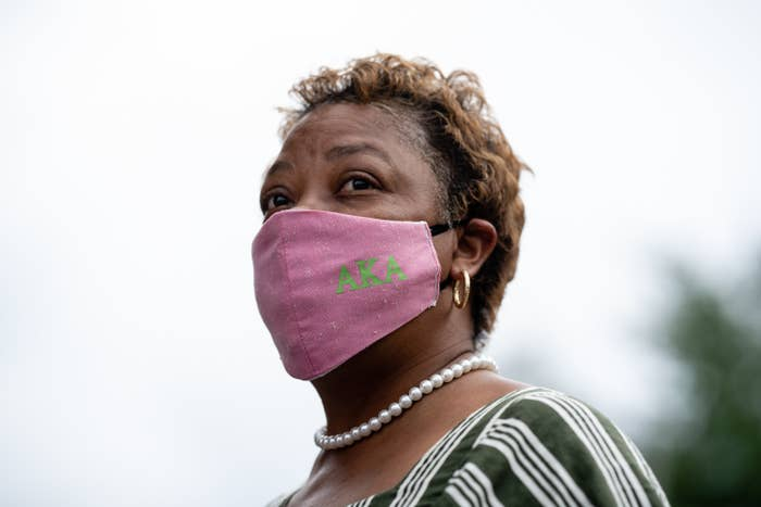 A woman wearing a pink face mask with AKA written in green on it