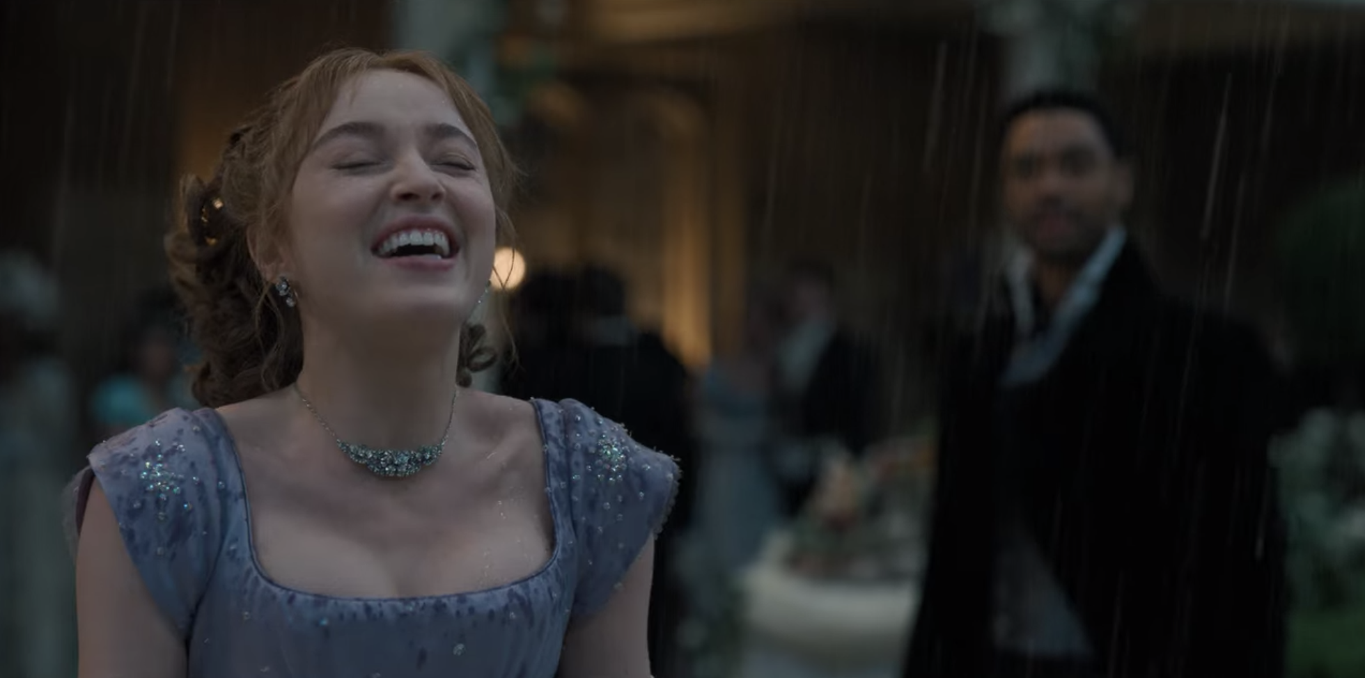 Daphne laughing in the rain as Simon looks at her with love