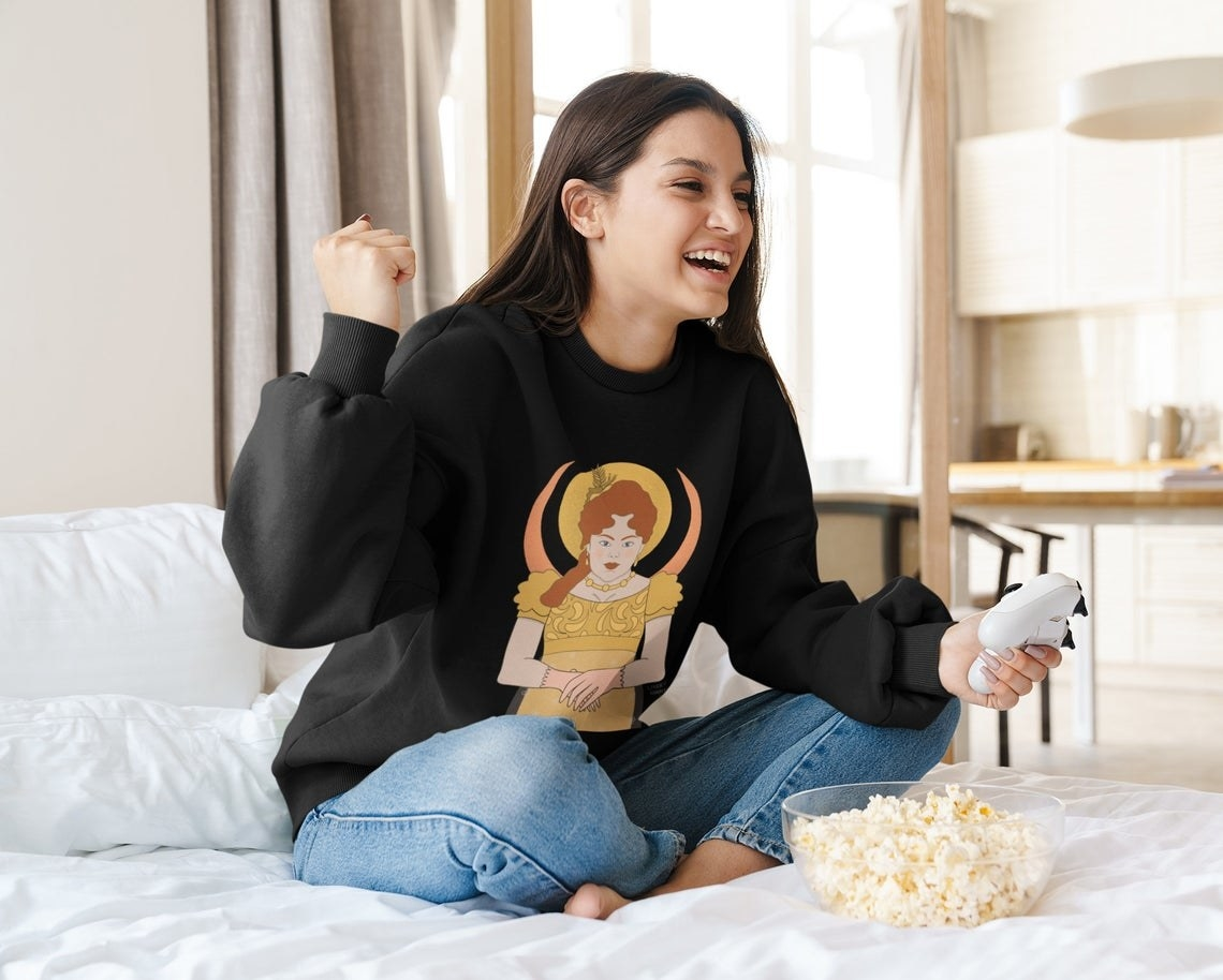 A person wearing the sweatshirt while eating popcorn and holding a gaming remote