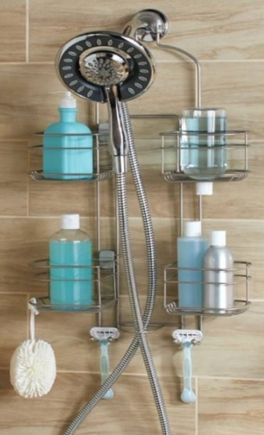 silver adjustable shower caddy in a shower holding bottles, sponge, and razors