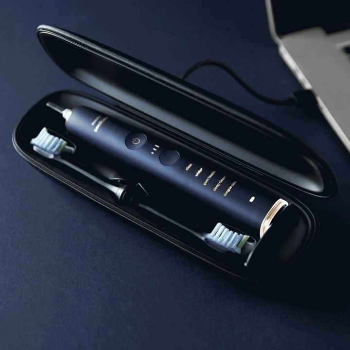 The toothbrush and two replacement heads inside the portable charging case