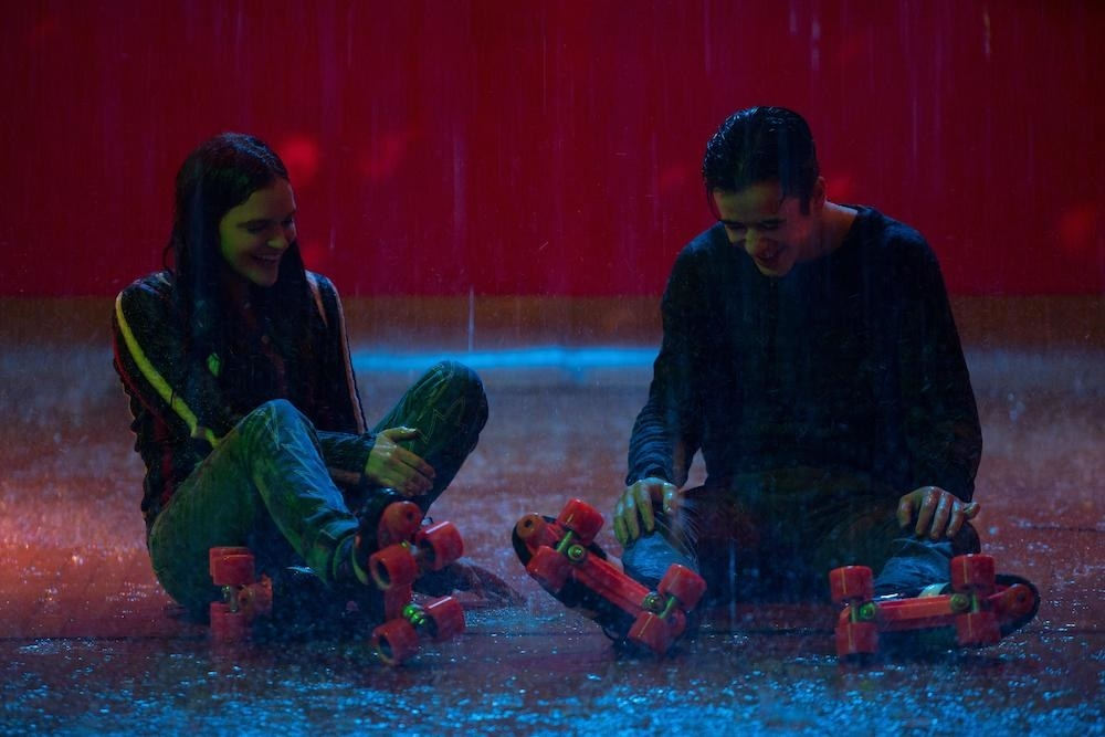 Marcus and Wendy sitting on the floor of a wet roller rink