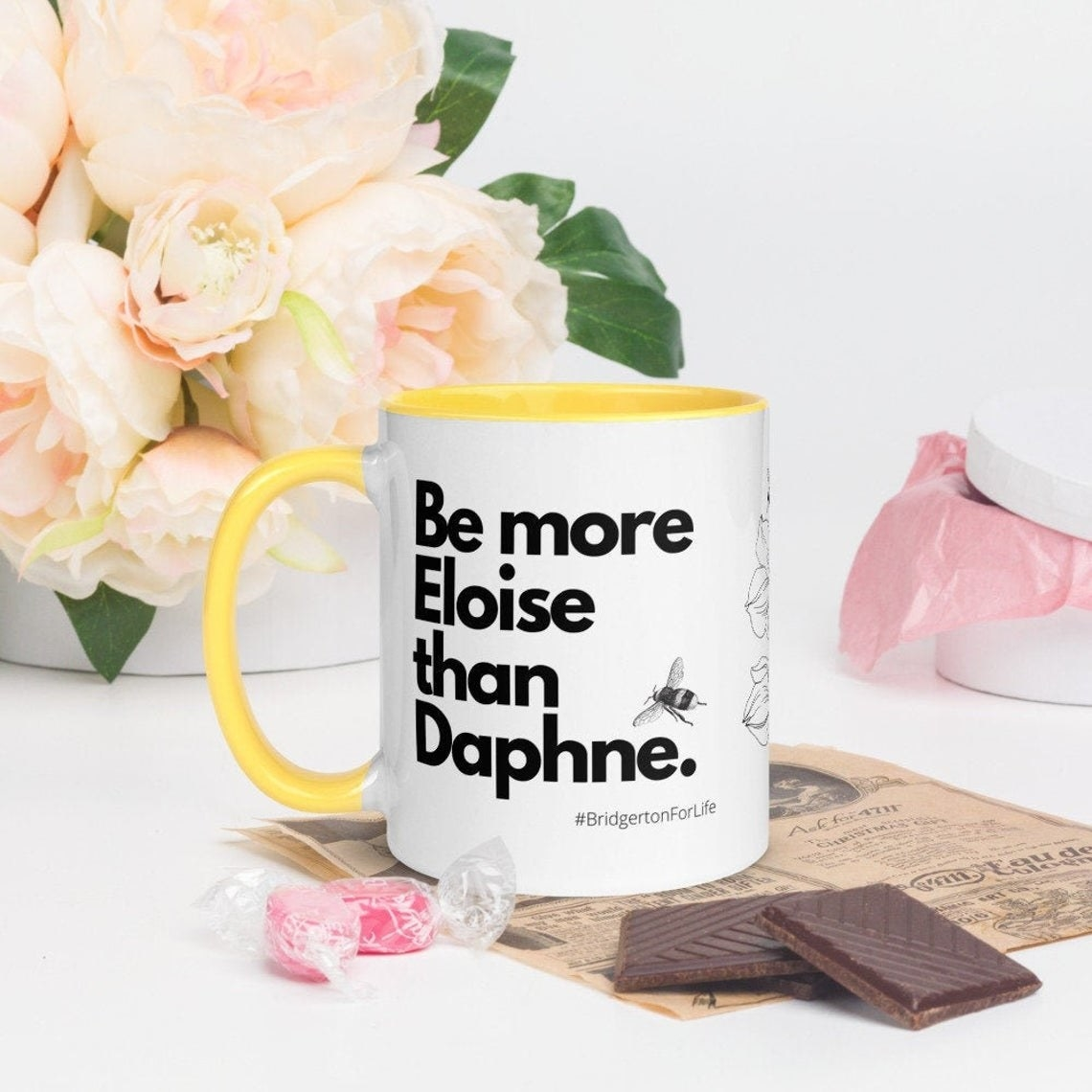 The mug surrounded by flowers and chocolate