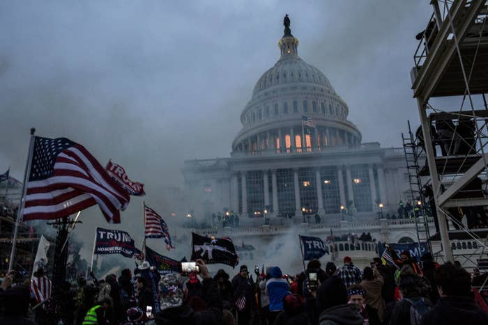 Insurrectionists storm the Capitol waving US and Trump flags as smoke billows through the night air