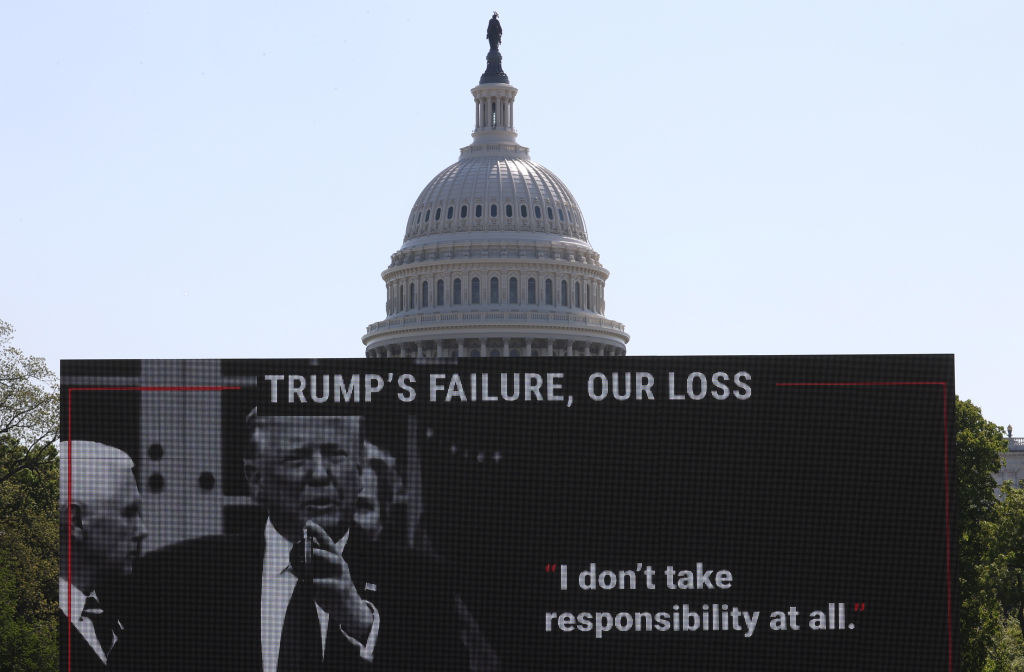"A large sign featuring Trump and former Vice President Mike Pence says ""Trump's Failure, Our Loss"""