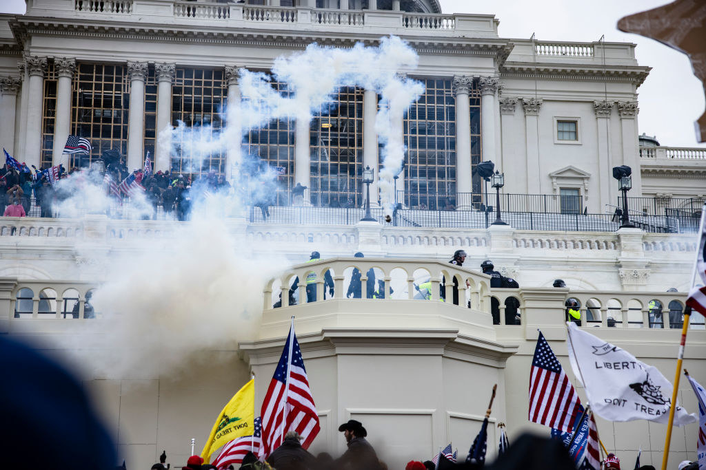 Smoke flowing into the air as Trump-supporting insurrectionists breach the Capitol steps
