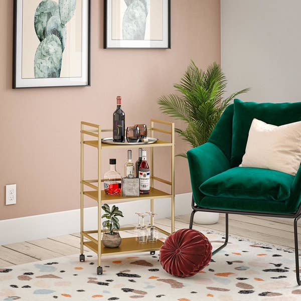 gold-finished metal cart in living room with wine and other bottles