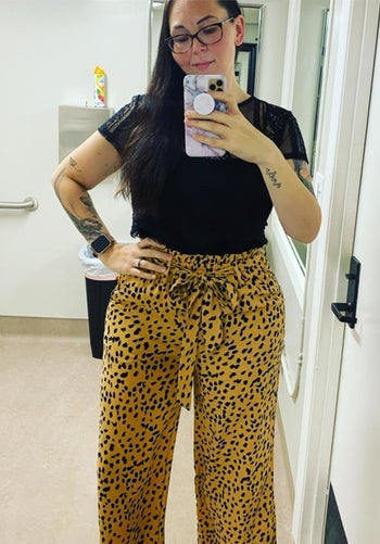 A reviewer wearing the pants in khaki and navy dot