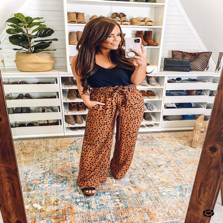 A reviewer wearing the pants in leopard