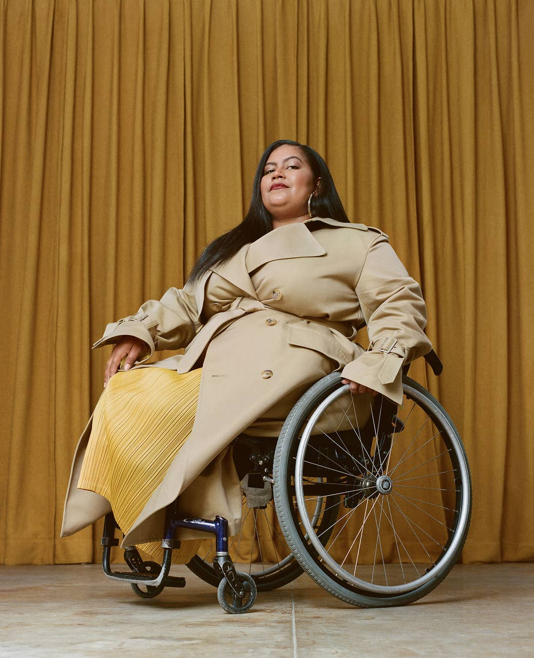 A woman in a trenchcoat and a wheelchair poses for a portrait