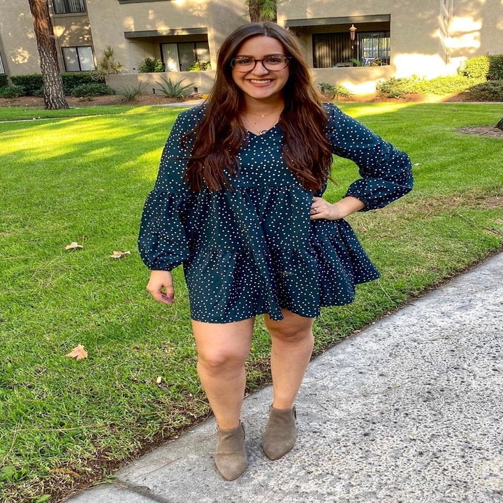 A reviewer wearing the dress in green polka dot
