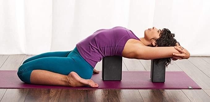 Woman stretching using the yoga blocks.