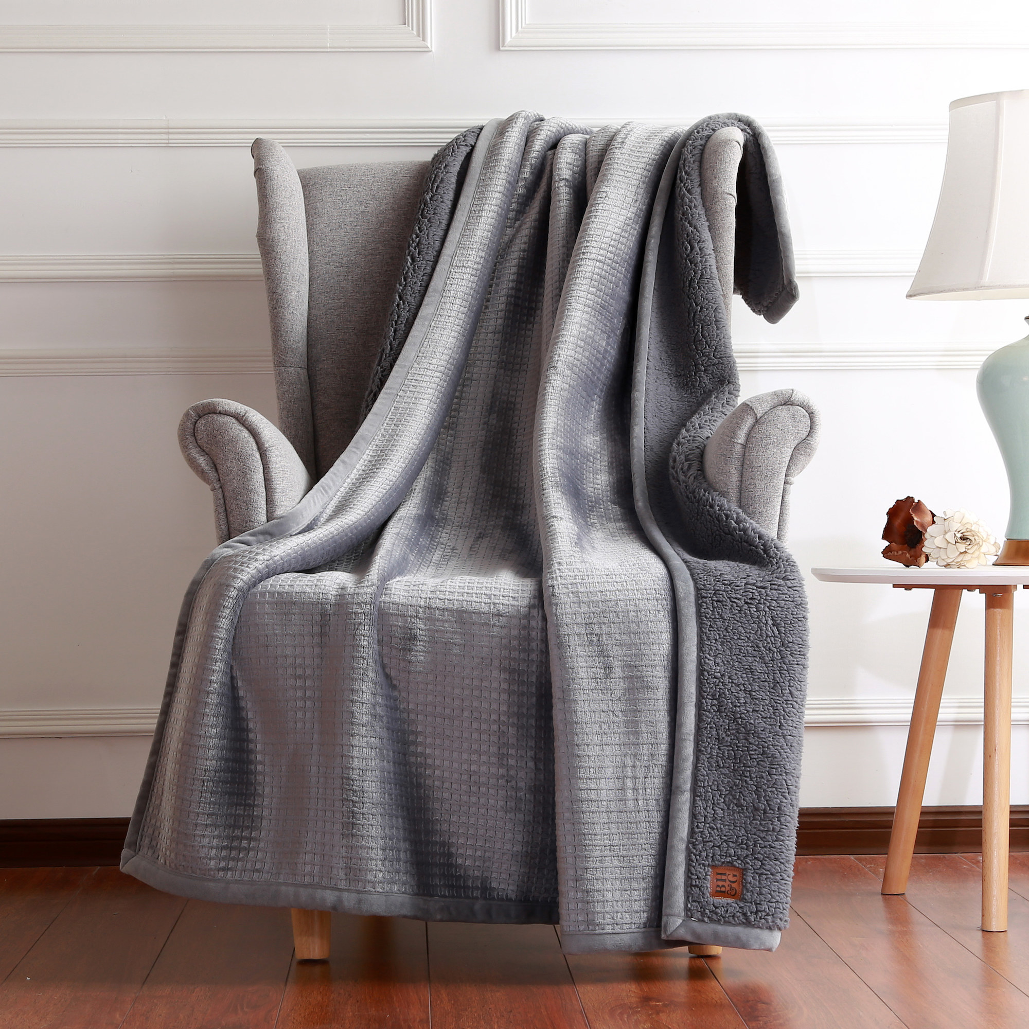 the throw in gray draped over a chair