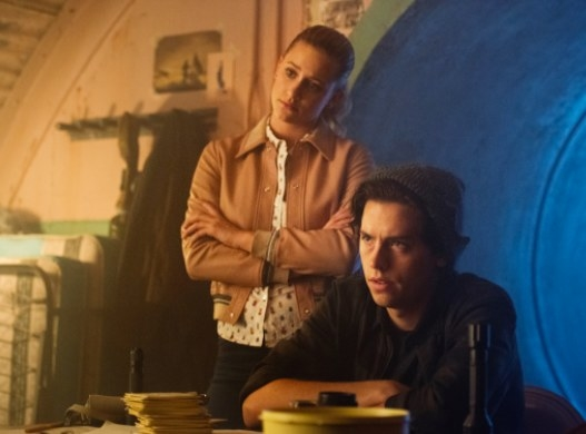 Betty stands behind Jughead in a bunker; they both have their arms crossed