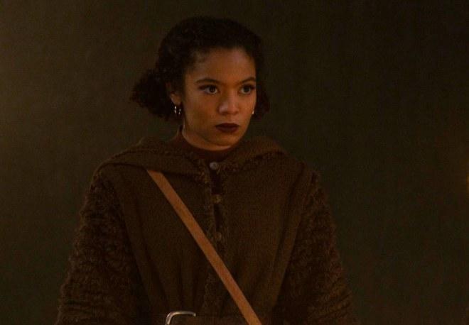 Roz stands in a dark cloak