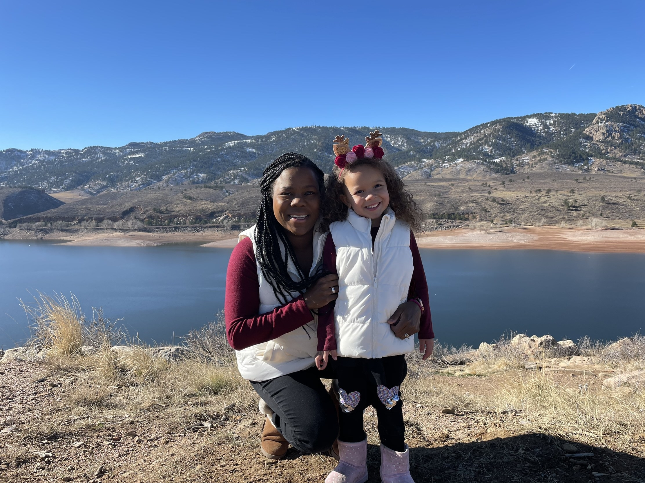 Melissa Burt poses with her young daughter in front of mountains and a lake