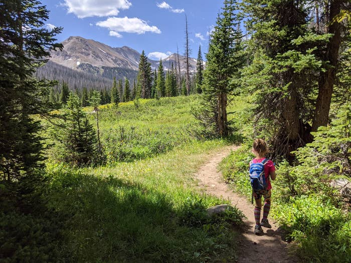 Emily Fischer's young child is on the side of a lush hiking trail, with mountains in the distance