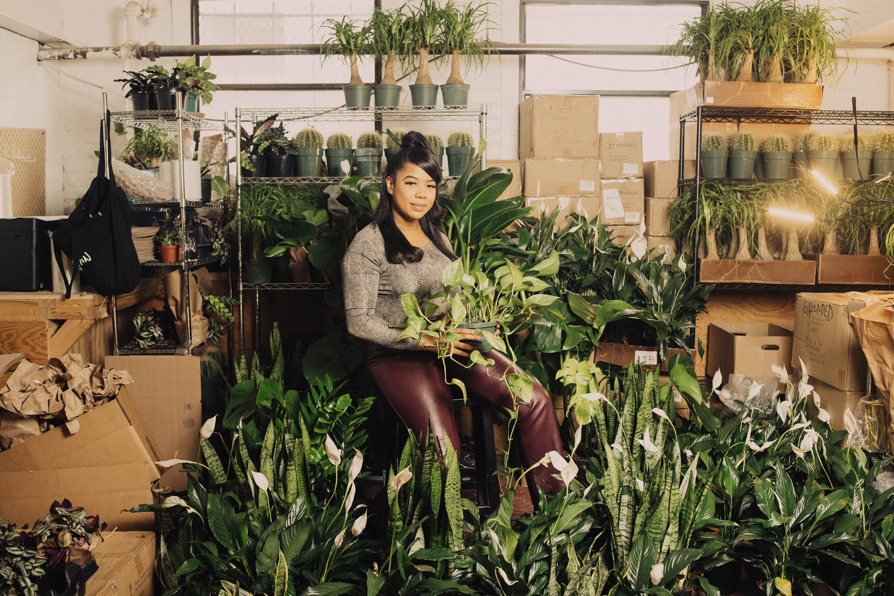 A woman sitting among many plants in a store she owns