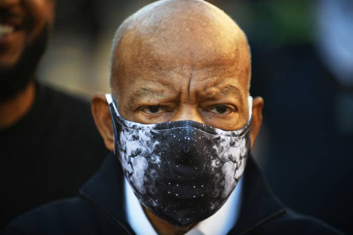 A older man is wearing a face mask and looking away from the camera