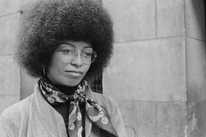 A woman with an afro and glasses stands in front of a stone building.
