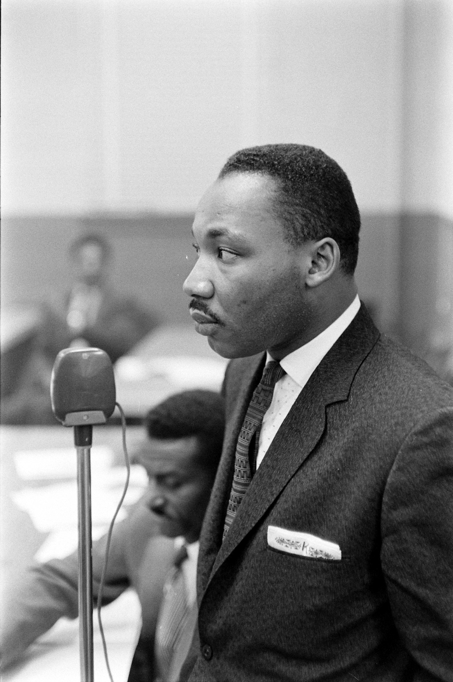 A man wearing a suit stands at a microphone.