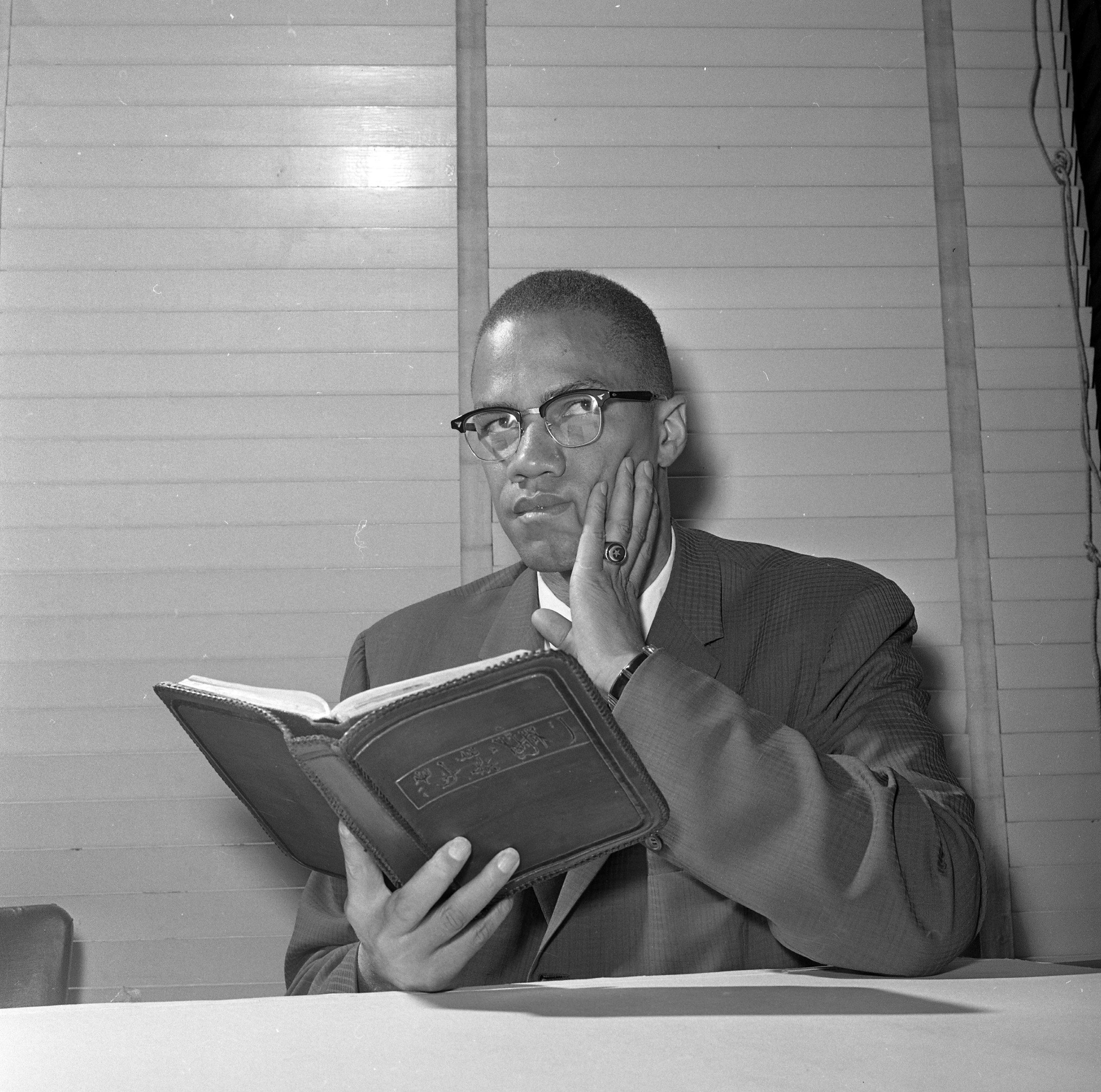 A man sits with his palm on the left side of his face and holds an open book in his other hand.