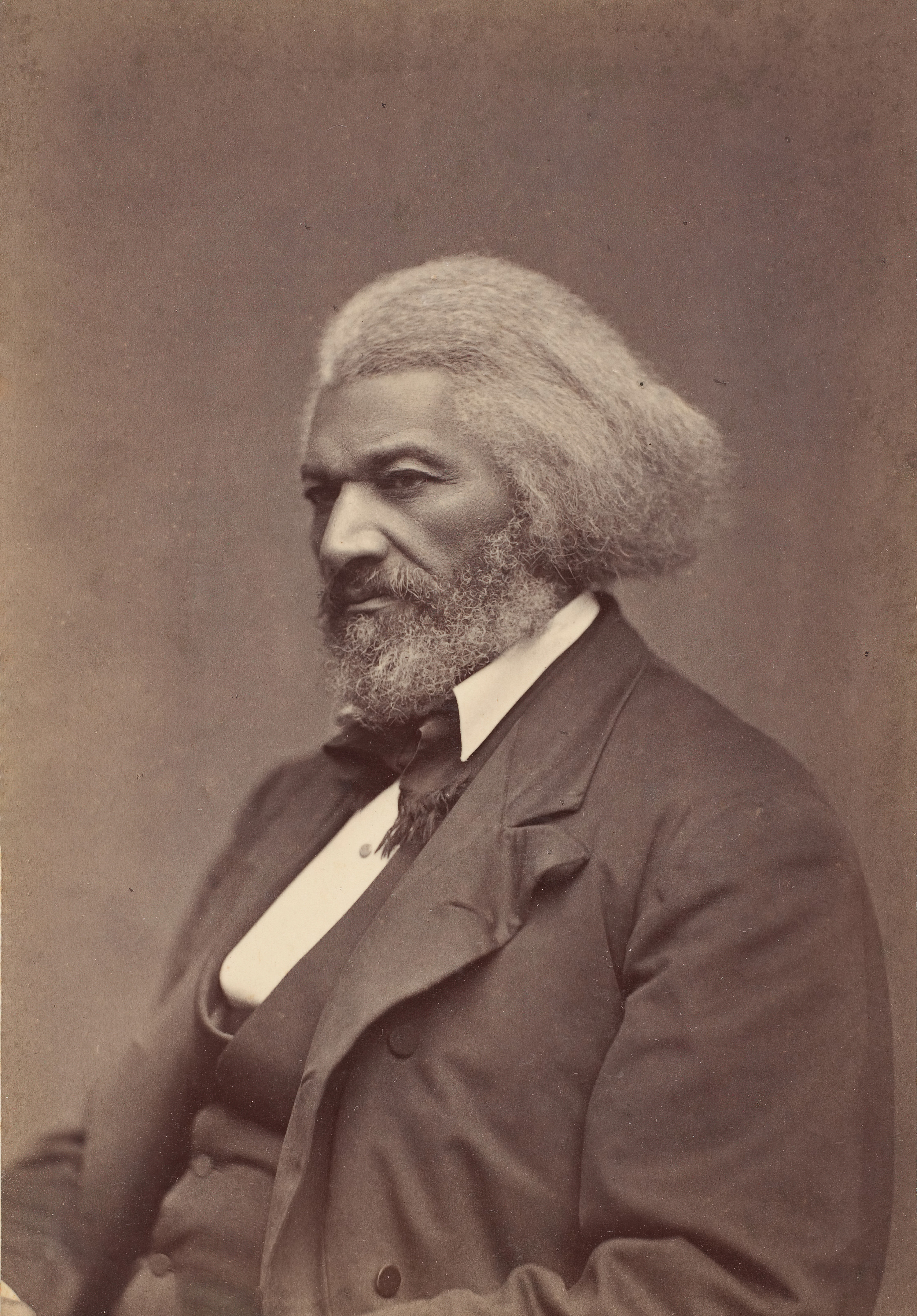 A man is wearing a suit in a profile portrait photo.