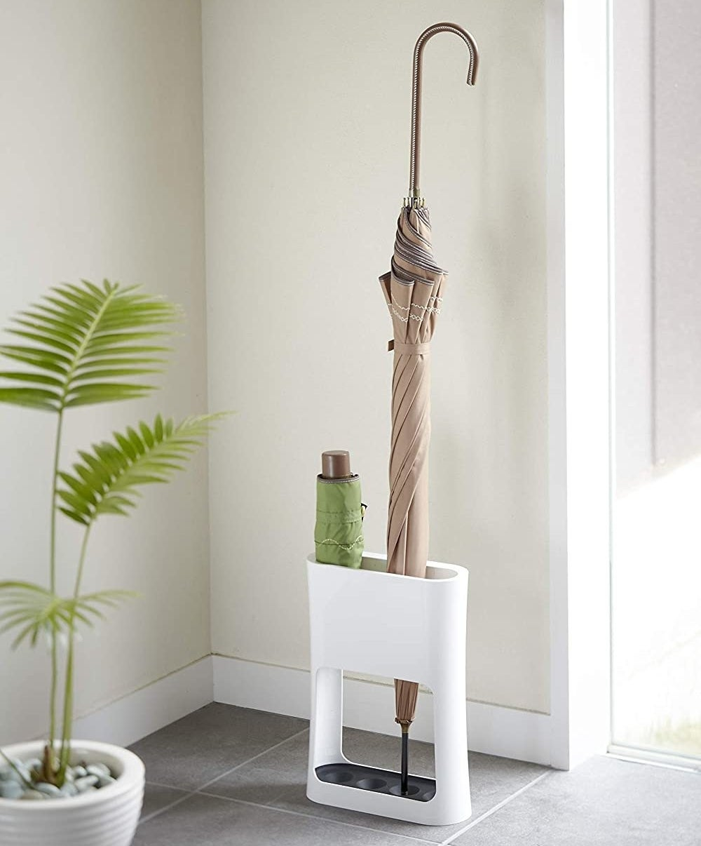 The umbrella stand with a large umbrella and a small portable one sitting inside