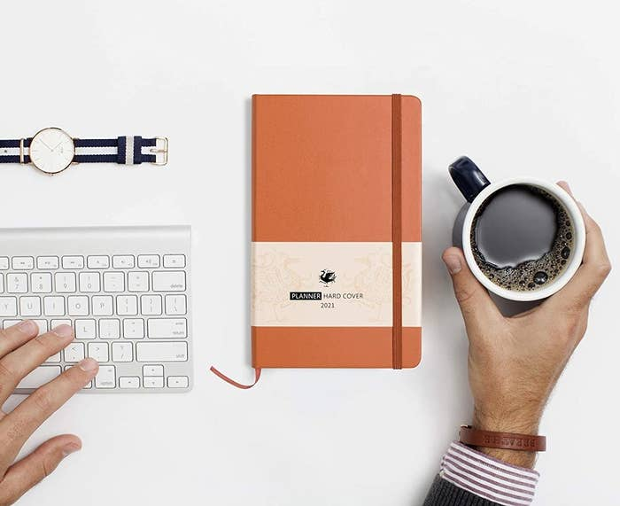 The agenda next to a keyboard, watch, and person holding a cup of coffee