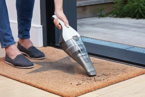 A person using the handheld vacuum to clean off a door mat