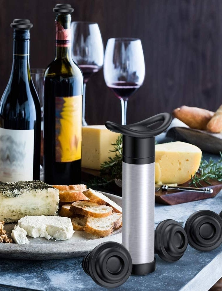 The vacuum pump and stoppers next to wine and cheese