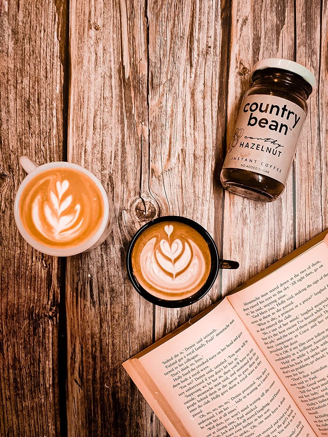Two cups of coffee pictured with a book.