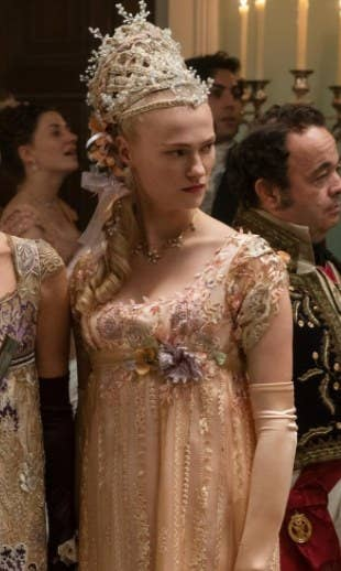 Cressida wears a complicated hairpiece and embroidered, embellished gown