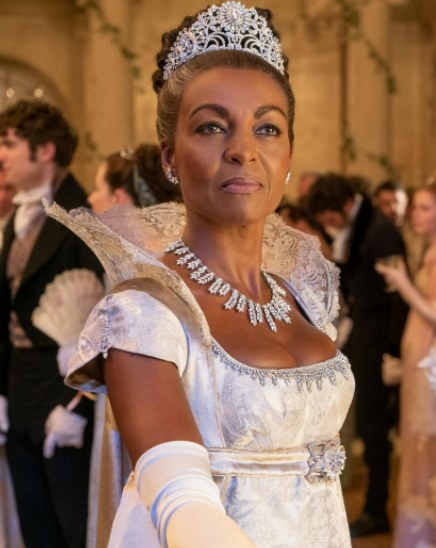 Lady Danbury wears a white and silver ball gown with a high lace collar