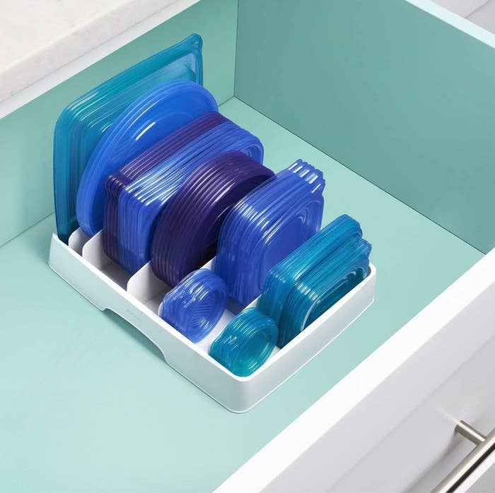 The organizer in a drawer filled neatly with food storage container lids