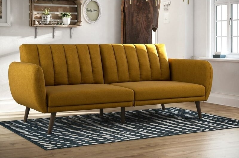 a mustard upholstered convertible couch in a living room